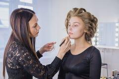 Maskenbildner, der flüssige Ton- Grundlage auf dem Gesicht der Frau anwendet Lizenzfreies Stockbild
