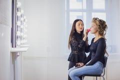 Maskenbildner, der flüssige Ton- Grundlage auf dem Gesicht der Frau anwendet Lizenzfreie Stockbilder