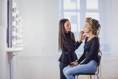 Maskenbildner, der flüssige Ton- Grundlage auf dem Gesicht der Frau anwendet Stockfotos
