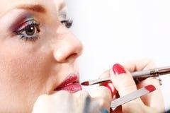 Maskenbildner, der Lippenstift auf vorbildlichen Lippen mit Bürste anwendet lizenzfreies stockfoto