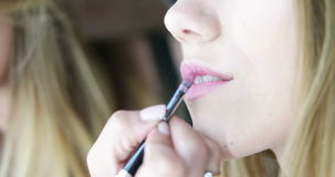 Maskenbildner, der Lippenstift vor dem Spiegel anwendet stock footage
