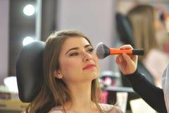 Maskenbildner, der Make-up am Modell im Schönheitssalon anwendet Lizenzfreie Stockbilder