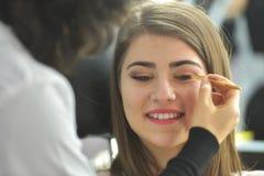 Maskenbildner, der Make-up am Modell im Schönheitssalon anwendet Lizenzfreie Stockfotos