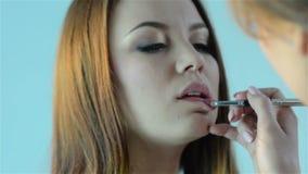Maskenbildner, der roten Lippenstift mit einer Bürste auf den Lippen einer jungen Schönheit anwendet stock video footage