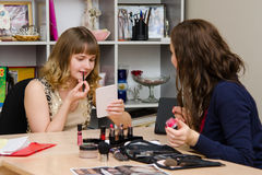 Maskenbildner erklärt dem Mädchen als Lippenstift Stockfoto