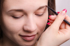 Maskenbildner holt Augenbrauenbürstenmodell Stockbilder