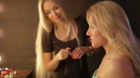 Maskenbildner macht ein Mädchen schönes Make-up vor einem wichtigen Ereignis die Frau, die Kosmetik mit einer Bürste aufträgt, bi stock video footage