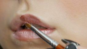 Maskenbildner macht Make-upmädchenmodell Lippenstiftlichtschatten traf mit einer speziellen Bürste auf den Lippen zu, die herau stock footage