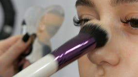 Maskenbildner macht Make-upmädchenmodell Spezielle Bürste wendet Abdeckstiftgrundlage im Schönheitssalon auf dem Gesicht des M stock video