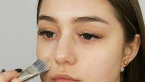 Maskenbildner macht Make-upmädchenmodell Spezielle Bürste wendet Abdeckstiftgrundlage im Schönheitssalon auf dem Gesicht des Mädc stock video footage