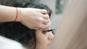 Maskenbildner Paints The Eyelashes f?r den M?dchen-Kunden stock footage