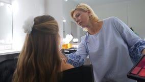 Maskenbildner setzt Pulver auf das Gesicht des Mädchens stock video