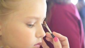 Maskenbildner-Stylist-Handeln bildet im Studio für das Jugendlich-Mädchen stock footage
