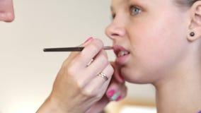 Maskenbildner-Stylist-Handeln bildet im Studio für das Jugendlich-Mädchen stock video