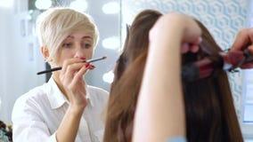 Maskenbildner und Friseur, die das Berufsanreden für junge Frau im Ausstellungsraum tun stock video footage