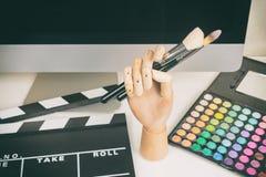 Maskenbildnerarbeitsplatz mit Make-uppalette mit Bürsten, Tastatur, Computermonitor, Schindel lizenzfreie stockfotografie