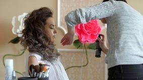 Maskenbildnerstilist arbeitet mit Modell Friseur tut das Haaranreden des Modells Sprühen der Festlegungsflüssigkeit von stock video footage