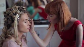 Maskenbildnerstilist, der Make-up für Modemädchen tut stock video