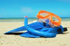 Masker en vinnen op een strand Stock Foto