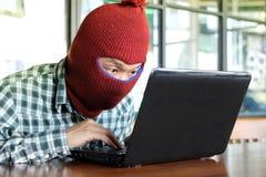 Maskerad en hacker som bär en balaclava som stjäler data från bärbara datorn för internetframförande för begrepp 3d säkerhet Arkivfoto