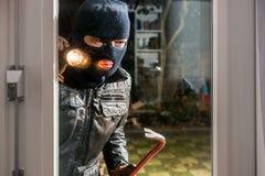 Maskerad inbrottstjuv med ficklampan och kofoten som ser in i exponeringsglaswi Arkivbilder