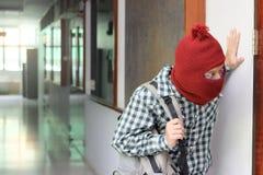 Maskerad inbrottstjuv med påsar som skriver in in i huset som är klart att begå brott Royaltyfria Bilder