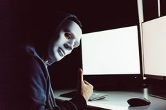 Maskerad och anonym en hacker under huven som ger upp tummar, medan genom att använda en dator med den tomma tomma vita skärmen i arkivbild