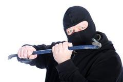 Maskerad rånare som hanterar en kofot Arkivbild