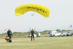 Maskerad skydiver som in kommer för att landa på gräs med öppet ljust Fotografering för Bildbyråer
