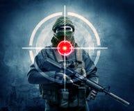 Maskerad terroristman med vapen- och laser-målet på hans kropp royaltyfri foto