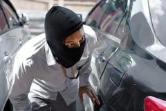 Maskerad tjuv i den svarta balaclavaen som försöker att bryta in i bilen royaltyfria foton