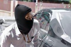 Maskerad tjuv i den svarta balaclavaen som försöker att bryta in i bilen royaltyfria bilder