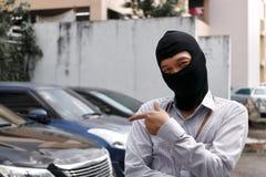Maskerad tjuv i den svarta balaclavaen som försöker att bryta in i bilen fotografering för bildbyråer