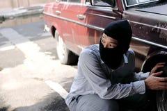 Maskerad tjuv i den svarta balaclavaen som försöker att bryta in i bilen Brottsligt brotts- begrepp royaltyfri fotografi