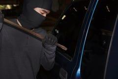Maskerad tjuv med balaclavaen genom att använda kofoten till avbrott in i en bil vägg för skugga för pistol för holding för brott royaltyfri fotografi