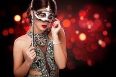 Maskerade-Karnevalsmaske der vorbildlichen Frau der Schönheit tragende venetianische an der Partei über Feiertagsdunkelheitshinte stockfotografie
