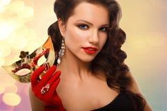 Maskerade-Karnevalsmaske der vorbildlichen Frau der Schönheit tragende venetianische an der Partei über dunklem Hintergrund des F stockfoto