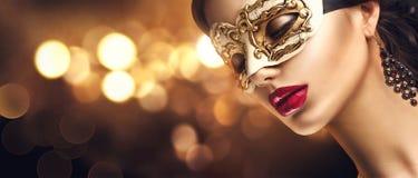 Maskerade-Karnevalsmaske der vorbildlichen Frau der Schönheit tragende venetianische an der Partei stockfotografie