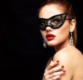 Maskerade-Karnevalsmaske der vorbildlichen Frau der Schönheit tragende venetianische an der Partei lokalisiert auf schwarzem Hint Lizenzfreie Stockfotos