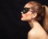 Maskerade-Karnevalsmaske der vorbildlichen Frau der Schönheit tragende venetianische an der Partei lokalisiert auf schwarzem Hint lizenzfreie stockfotografie
