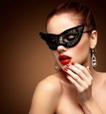 Maskerade-Karnevalsmaske der vorbildlichen Frau der Schönheit tragende venetianische an der Partei lokalisiert auf schwarzem Hint Stockfoto