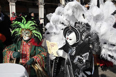 Maskerade personer i färgrik dräkt med fjäderdräktsammanträde i kafé Royaltyfria Foton