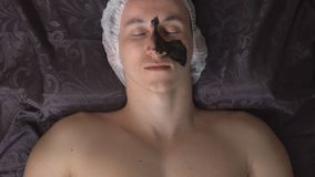 Maskering för framsidan Bästa sikt av en avkopplad ung man, medan applicera en svart maskering i brunnsorten stock video
