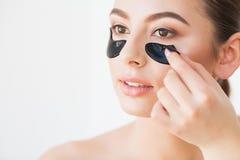 Maskering f?r hudomsorg Kvinna med svarta lappar arkivbild