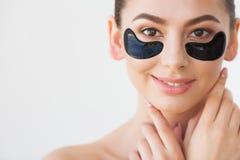 Maskering f?r hudomsorg Kvinna med svarta lappar royaltyfria foton