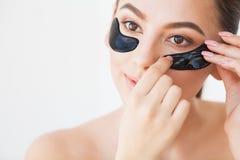 Maskering f?r hudomsorg Kvinna med svarta lappar royaltyfri bild