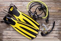 Maskering, fena, snorkel och regulator på träskrivbordet Royaltyfri Fotografi
