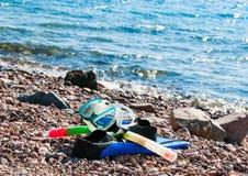 Maskering och flipper på stranden Royaltyfria Foton