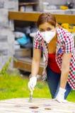 Maskering och handskar för ung kvinna som bärande målar en wood tabell Arkivfoto