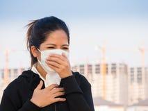 Maskering och hosta för framsida för asiatisk kvinna bärande fotografering för bildbyråer